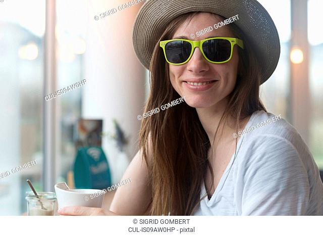 Young woman wearing straw hat and sunglasses drinking coffee in cafe