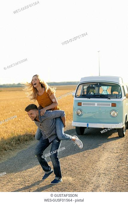 Playful young couple at camper van in rural landscape