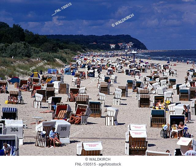Roofed wicker beach chairs and tourists on beach, Mecklenburg-Vorpommern, Germany