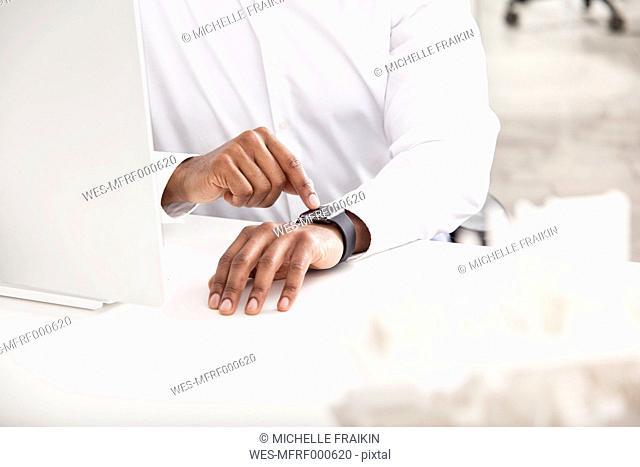 Man's hand adjusting smartwatch at desk