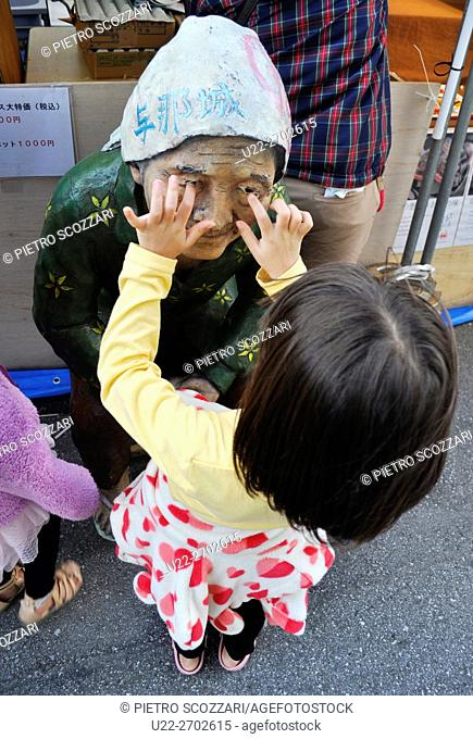 Naha, Okinawa, Japan: a little girl playing with the statue of a grandma