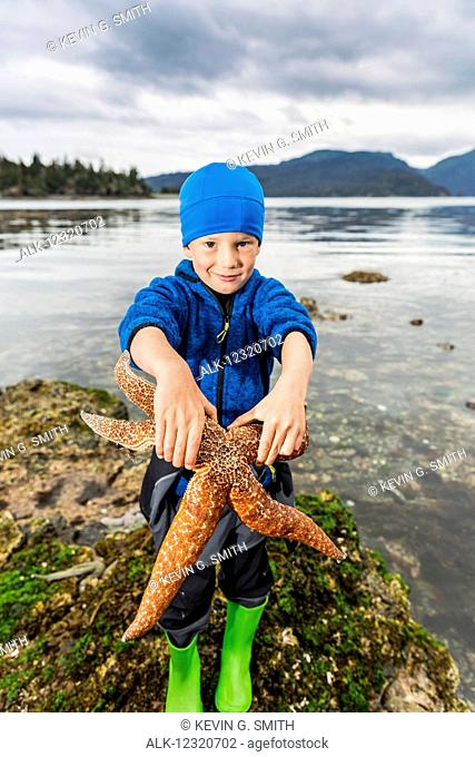 Young boy showing off a large sea star, Hesketh Island, Southcentral Alaska, USA