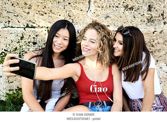 Three smiling young women sitting at stone wall taking a selfie