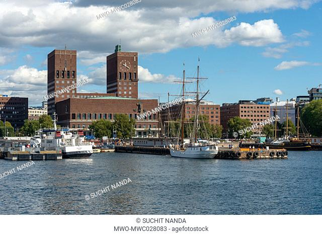 Aker brygge [båt], Ferry Terminal, Oslo, Norway. Oslo City Hall is built of red brick and has two towers, one 63 meters tall and other 66 meters tall