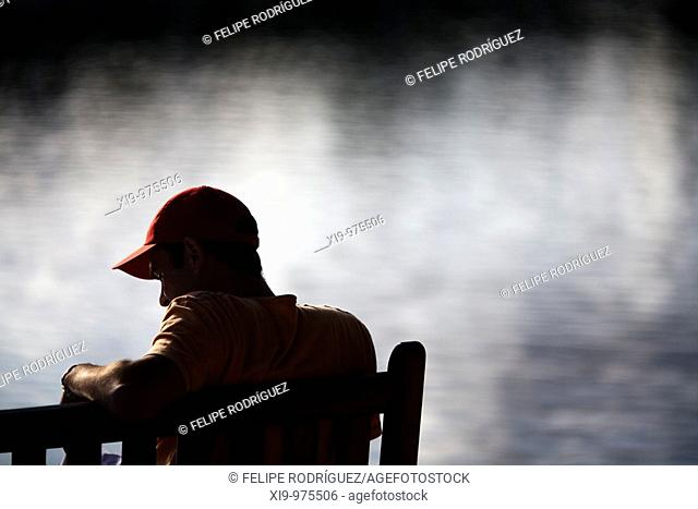 Young man sitting on a bench by the sea, Conleau island, town of Vannes, departament of Morbihan, region of Brittany, France