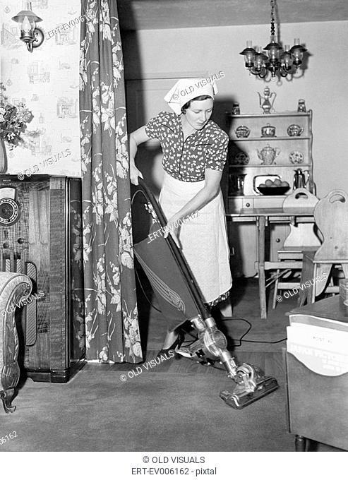 Woman doing housework with a vacuum cleaner All persons depicted are not longer living and no estate exists Supplier warranties that there will be no model...