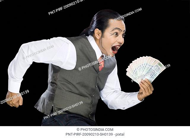 Close-up of a mime running with currency notes