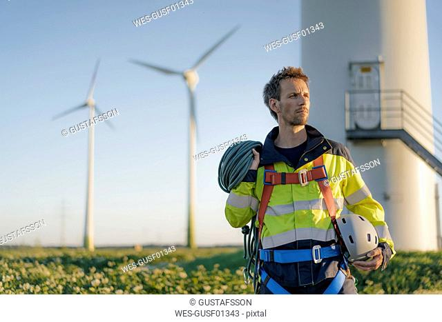 Technician standing at a wind farm with climbing equipment
