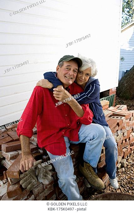 Portrait of a mature couple embracing while sitting on stack of bricks outside house