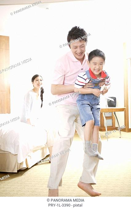Young man holding a son while woman sitting behind on bed, smiling