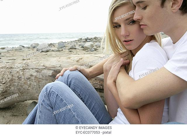Young affectionate couple embracing on beach, close-up