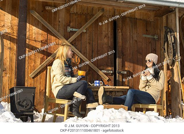 Two girlfriends have tea winter snow cottage sunny outdoor