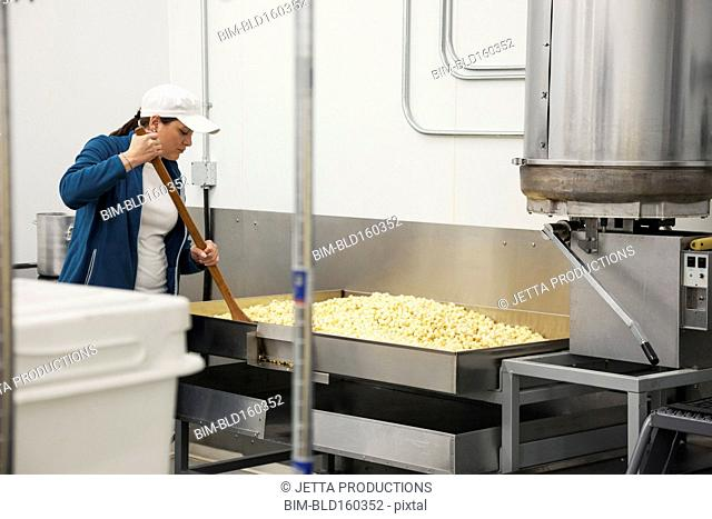 Caucasian worker stirring ingredients in factory