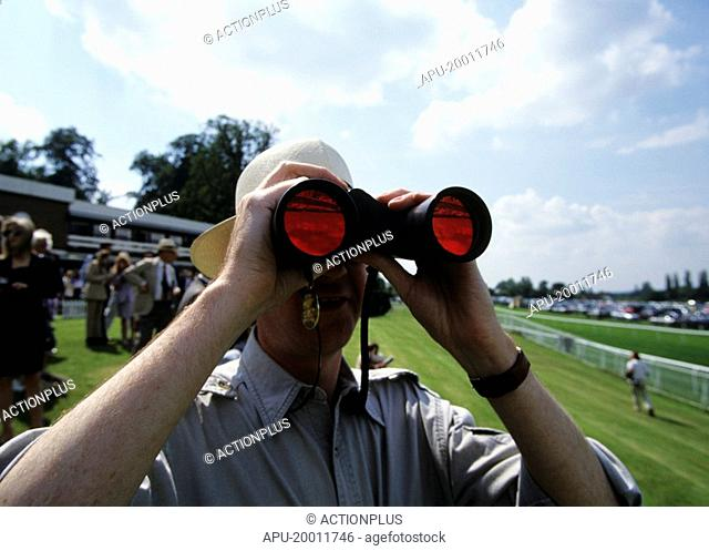 Man looking through binoculars at a race course