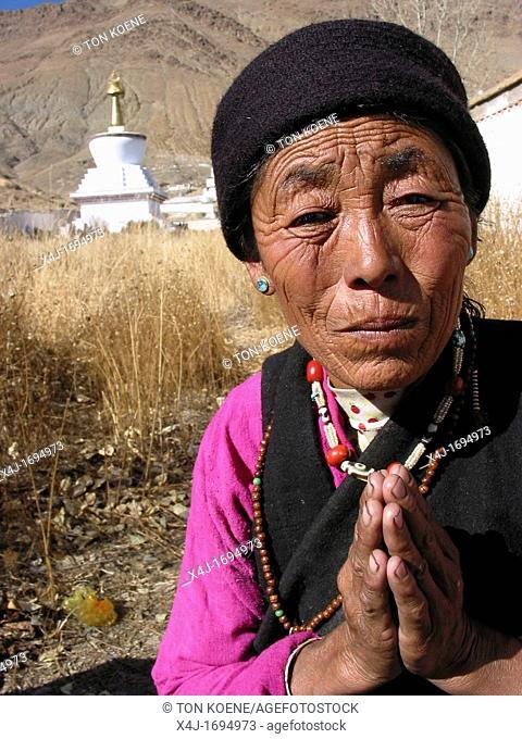 Woman is praying near a tomb, Xizang, Tibet