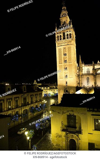 North view of the Giralda with Archbishop's Palace on the left at night, Seville. Andalusia, Spain