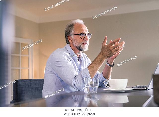 Mature man with laptop sitting at table at home