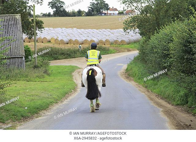 Woman riding a horse down quiet country lane, Bromeswell, Suffolk, England, UK
