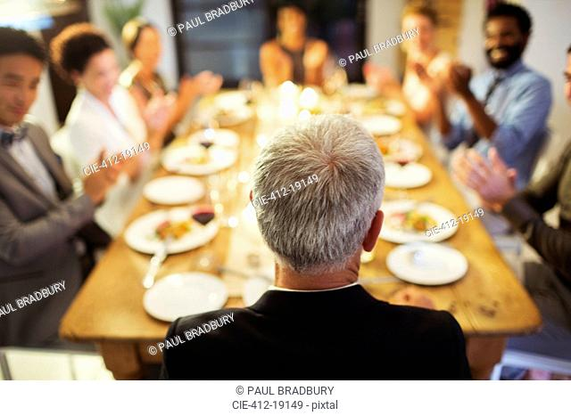 Friends applauding at dinner party