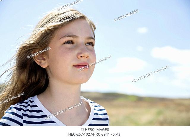 Thoughtful schoolgirl looking away outdoors