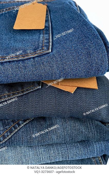 stack of folded blue jeans on a white background, close up