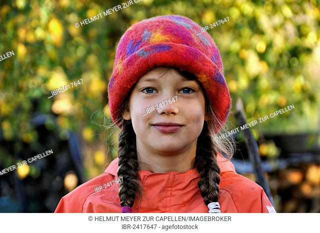Portrait of a girl with braids, eight years old, wearing a colorful felt hat, Othenstorf, Mecklenburg-Western Pomerania, Germany, Europe