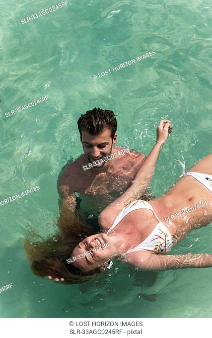 Couple playing in tropical sea