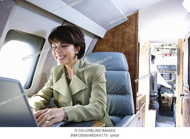 Businesswoman using laptop on private airplane