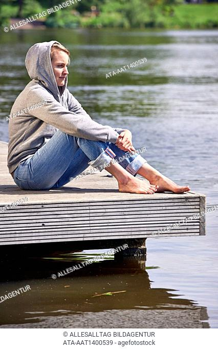 Woman sitting on a landing stage
