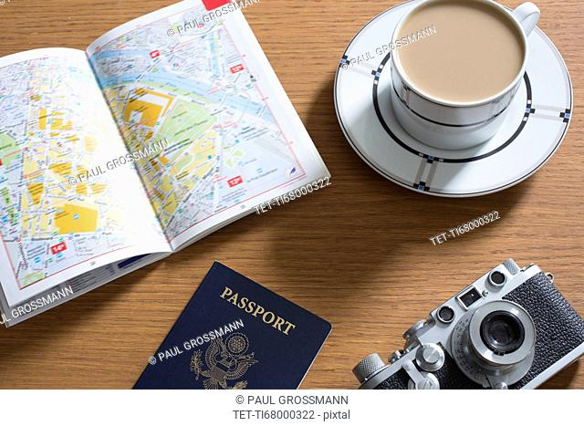 Passport, coffee, old camera and open guidebook