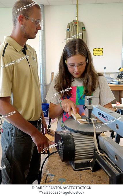 Teacher Showing 6th Grade Girl How to Use Scroll Saw, Wellsville, New York, USA