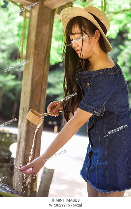 Young woman wearing blue dress and hat using bamboo water hand washing basins at Shinto Sakurai Shrine, Fukuoka, Japan