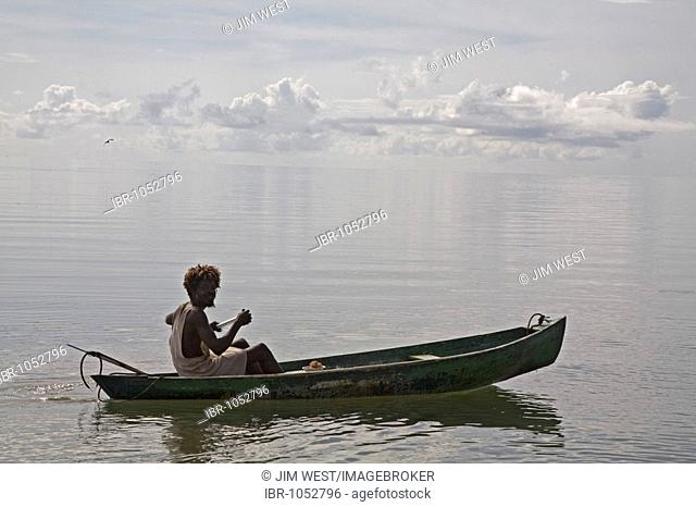 A young Garifuna man sets out in his canoe for some spear fishing in Hopkins Bay on the Caribbean Sea, Hopkins, Belize, Central America