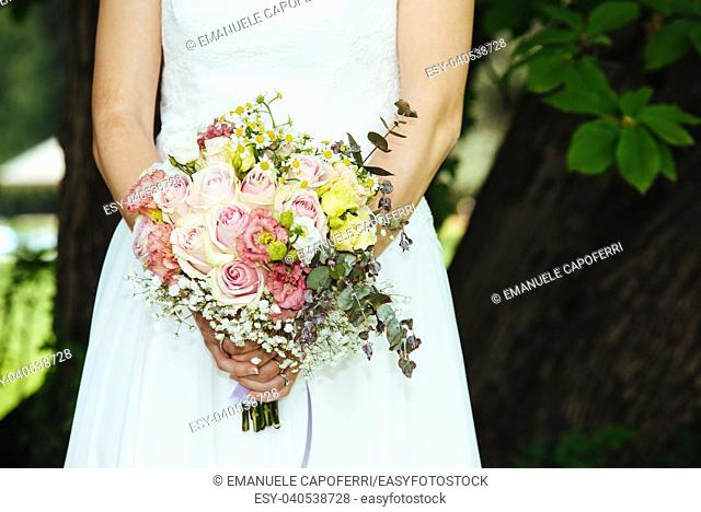 bride holds her bouquet of flowers with ivy roses daisies and hydrangeas in her wedding day