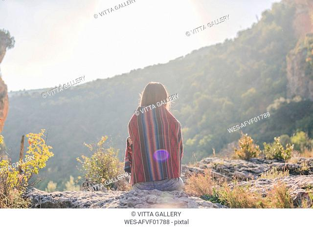 Spain, Alquezar, rear view of young woman on a hiking trip sitting on a rock