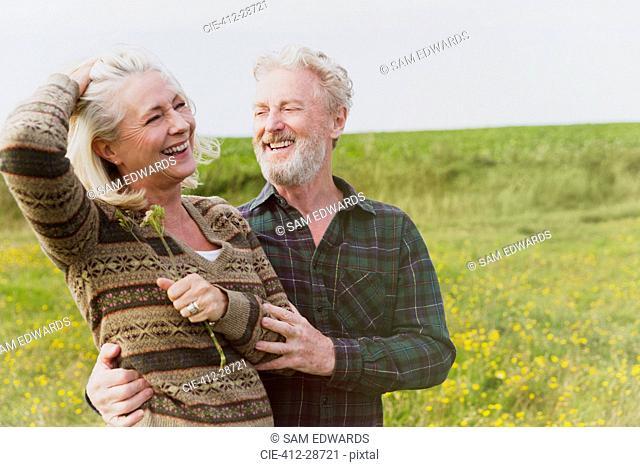 Smiling senior couple hugging in field