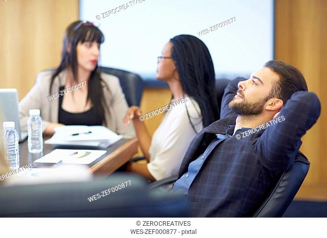 Businessman leaning back in boardroom