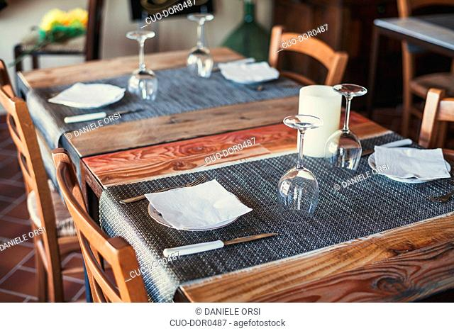 Light wooden table setting: white plates, rustic dark table cloth
