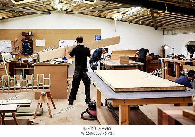 A furniture workshop making bespoke contemporary furniture pieces using traditional skills. Two men working with wood