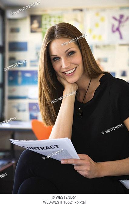 Young business woman checking contract, portrait