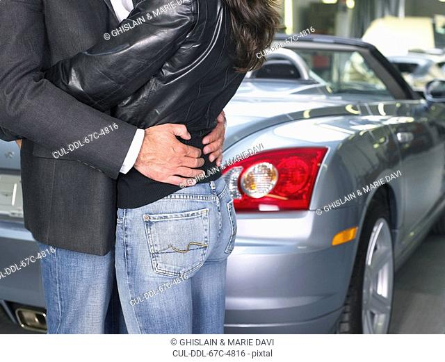 Couple holding each other in front of a convertible close up