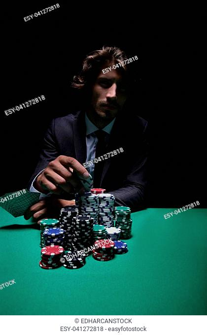 A man trying to make a decision on his strategy during a poker game