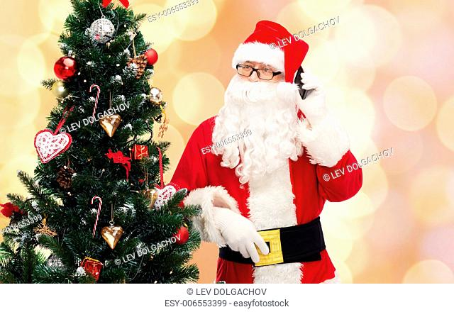 holidays, technology and people concept - man in costume of santa claus with smartphone and christmas tree over beige lights background