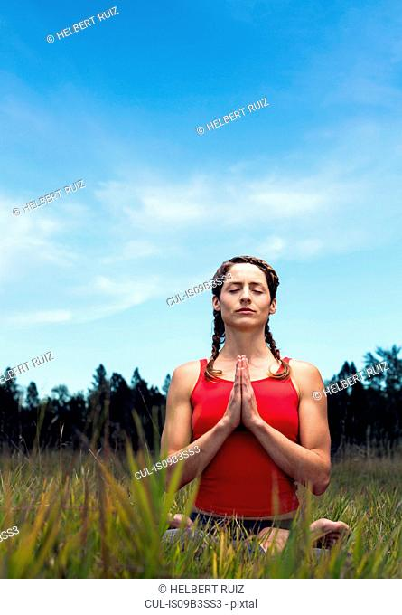 Young woman sitting in field, in yoga position