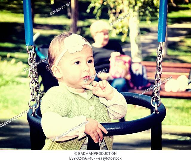 Little baby girl on the swing in park