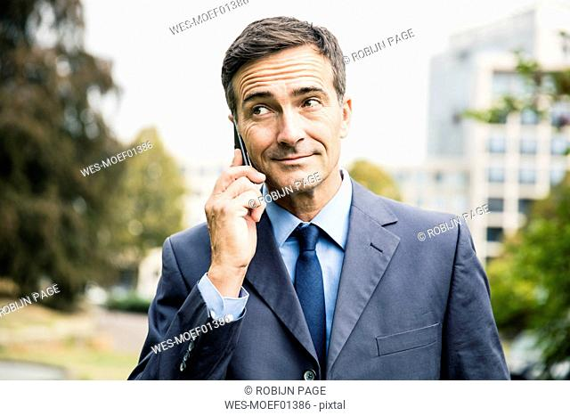Businessman on cell phone in city park