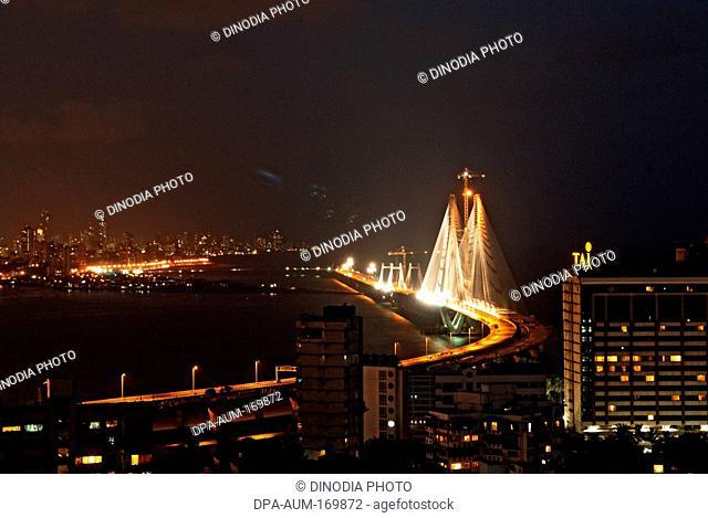 Illuminated bandra worli or rajiv gandhi sea link with bandra bandstand skyline ; Bombay Mumbai ; Maharashtra ; India 30-May-2009