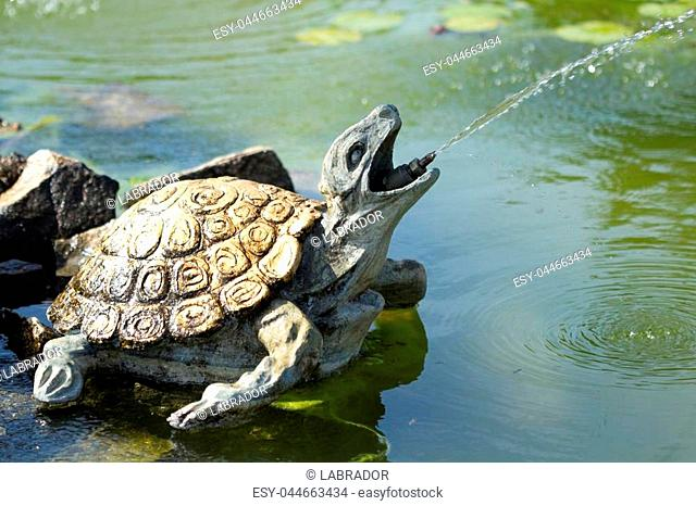 Bronze turtle fountain spraying water in France