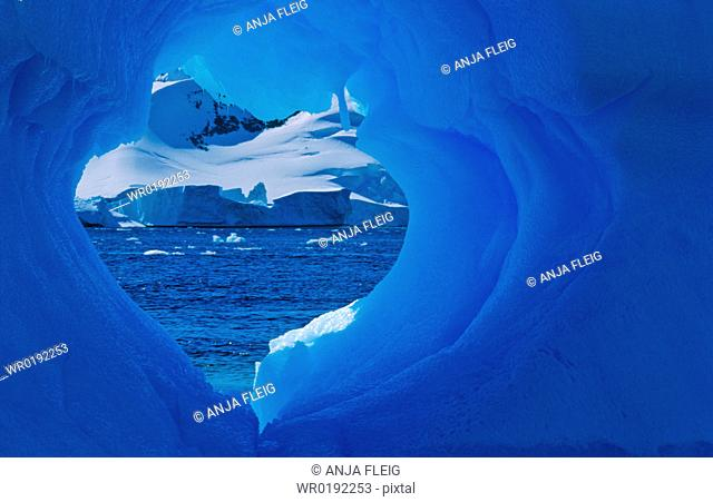 Heartshaped hole in an Antarctic blue iceberg PlÈneau Island, Antarctica