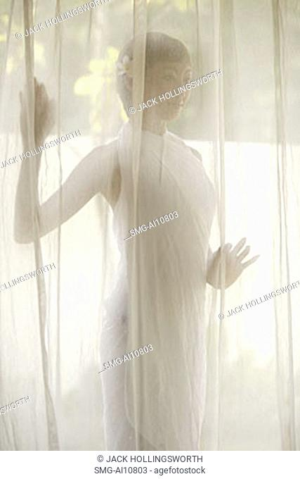 Young woman standing behind curtain